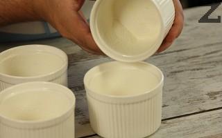 Намазват се с масло 4 купички за печене. Във всяка се слага по 1 лъжичка захар и разпределя по дъното на стените с въртеливи движения.