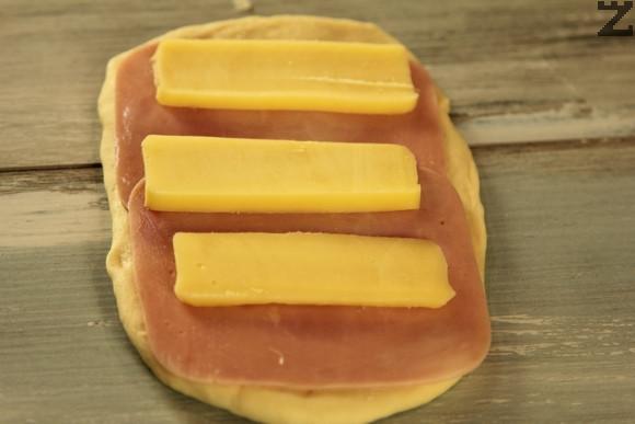 Тестото се разточва с валяк на правоъгълна форма върху набрашнен плот. Подреждат се шунка и кашкавал нарязани на тънки филии.