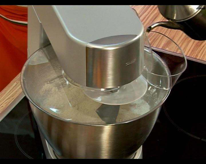 Разбъркваме брашното, солта и захарта с помощта на кухненски робот, който сме пуснали на най-ниската степен. Добавяме маята, разбъркваме, наливаме зехтина и отново разбъркваме.
