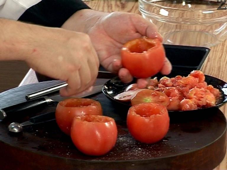 Отрязваме основата на всеки домат и издълбаваме сърцевината му, посоляваме.