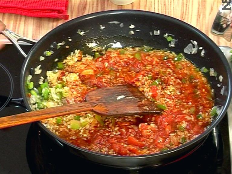 Връщаме ястието на котлона. Добавяме доматите, наливаме водата.