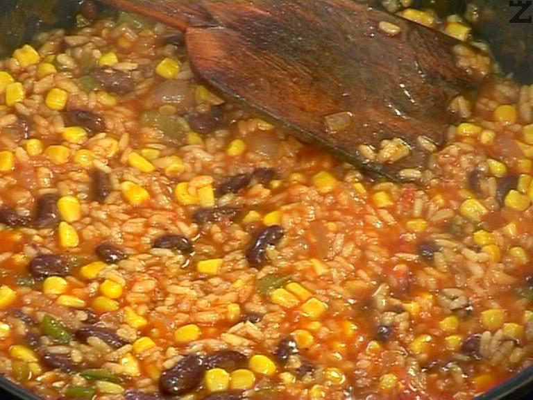 Изсипваме царевицата и червения боб, поръсваме с кимион и нарязан на ситно джоджен. Задушаваме ястието докато ориза поеме водата.