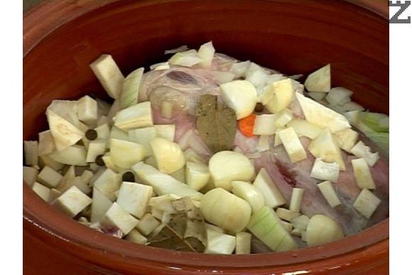 В глинения съд поставяме всички зеленчуци и месото. Поръсваме с подправките, добавяме нарязаните на дребно скилидки чесън.