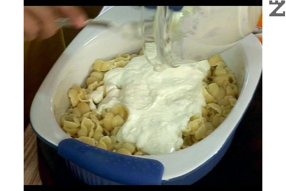 Изсипваме охладените макарони в тава, поливаме ги с киселото мляко.