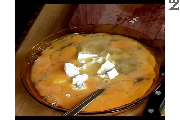 В чиния се разбиват яйцата с вилица и тогава се прибавя натрошеното на едро сирене.