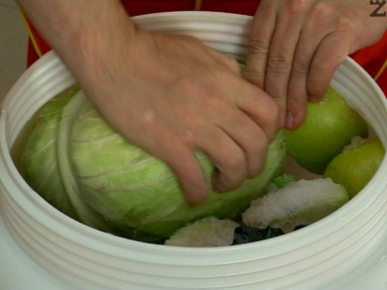 Поставяме зелките на дъното на бидона с разрязания кочан нагоре. Добавяме и останалите продукти, разрязани на големи парчета.