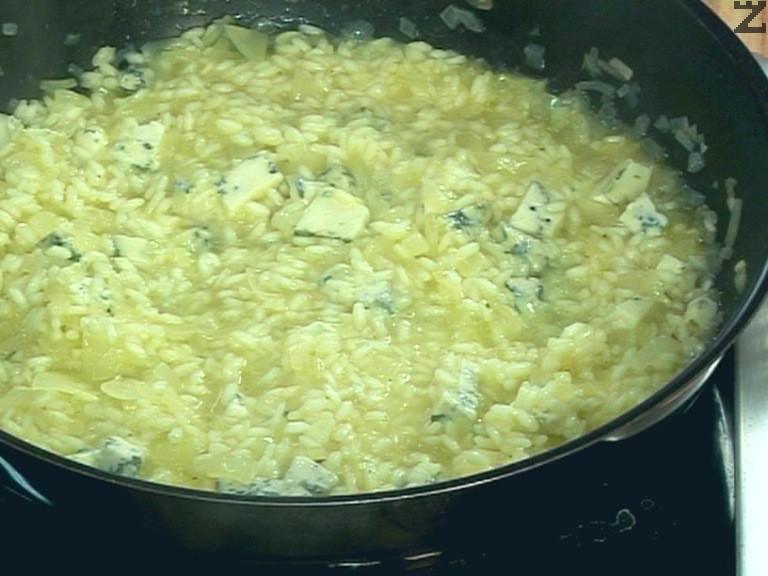 След като течността се изпари, добавяме още 300 мл от бульона, разбъркваме непрекъснато. Нарязваме синьото сирене на кубчета, прибавяме го към ориза. Оставя се да ври на бавен огън докато се изпари течноста.