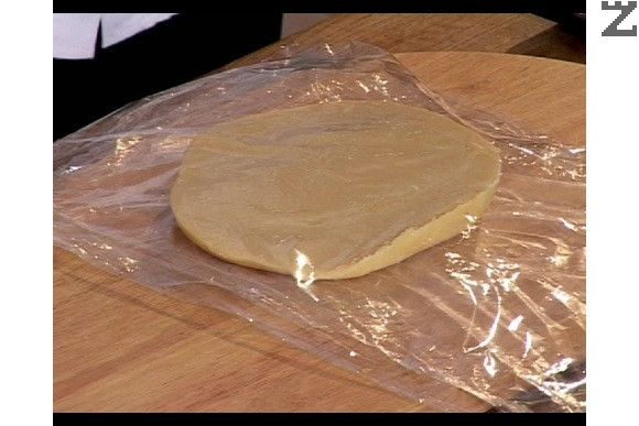 Охладеното тесто се разделя на две части. По голямата (2/3 от тестото) се разточва на тънка кора толкова голяма, че да покрие дъното и стените на тавата в която ще се пече., Останалата 1/3 тесто се връща в хладилника.