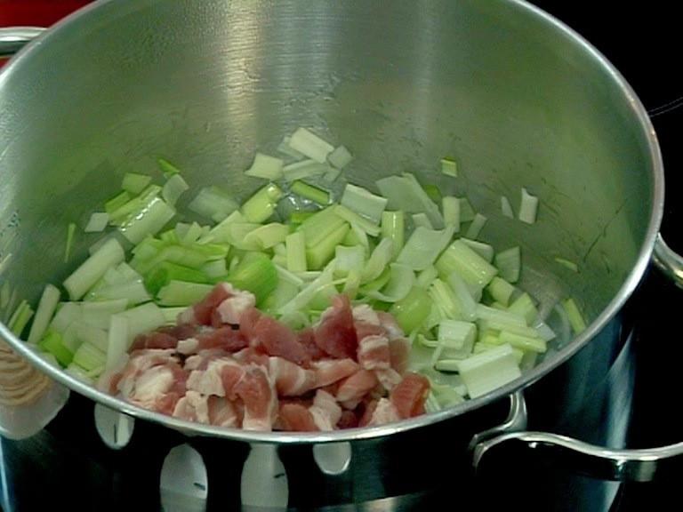 Нарязваме на малки парченца свинските гърди, добавяме ги при вече омекналия праз. След като се разбърка добре, на силен огън се пържи 3 минути без да се размесва за да се зачерви леко месото.