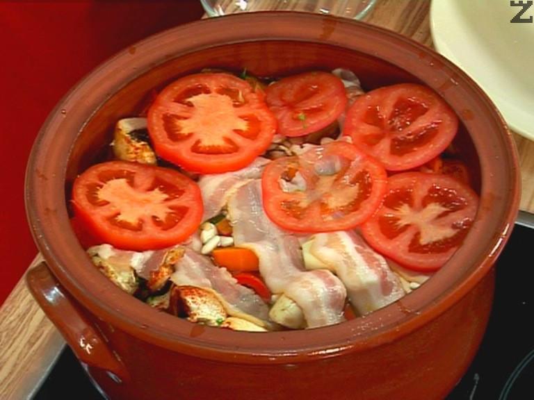 Покриваме с останалите филийки бекон, подреждаме нарязания на филийки домат. Заливаме с 200 мл гореща вода. Покрива се с капак и поставя в студена фурна, загрява се на 200-220 градуса за 30 мин. След това намаляваме фурната на 160 градуса и печем още 5 часа.