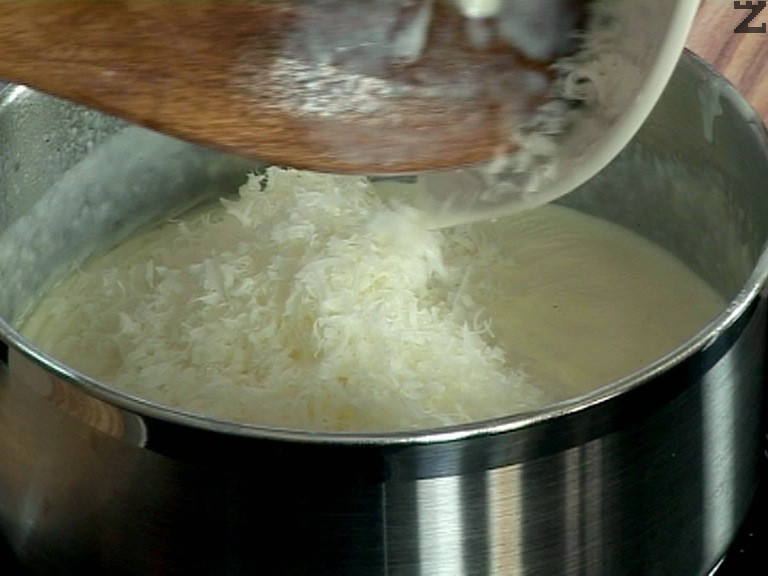 Връщаме на котлона, кипваме сместа, посоляваме, поръсваме с индийско орехче. Настръгваме сиренето, изсипваме го в горещия сос.