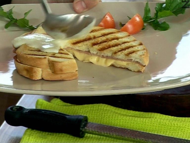 Готовите сандвичи се разрязват на две по диагонал, поставят се в чинии и се поднасят със соса.