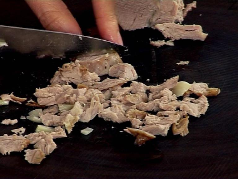 Нарязваме задушеното свинско филе - Аросто на дребни късчета. Запържваме го за кратко в зехтин заедно с целите скилидки чесън. Поръсваме със сол и черен пипер.