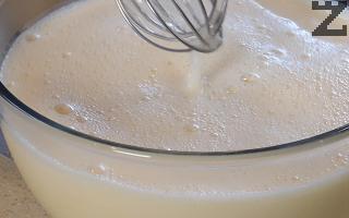 Отделно разбиваме за кратко с тел яйцата, постепенно ги смесваме с горещото мляко и ванилията. Добавяме лимоновата есенция.