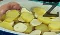 Намасляваме дъното и страните на тава за печене. Редим в следната последователност - ред картофи, посоляваме, отгоре подреждаме нарязания кашкавал, тънките филийки шунка, отново ред картофи, топено сирене и пак картофи.