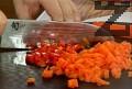 Нарязваме предварително сварените моркови на кубчета, наситняваме и чушките.