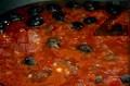 Наситняваме чесъна, запържваме за кратко в зехтин. Прибавяме маслините и каперсите, изливаме накълцаните на дребно домати. Поръсваме със сол и захар, оставяме да ври за 10 мин.