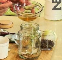 В буркан се налива оцет и се слага сол, захар, бахар, пипер, лук и копър.