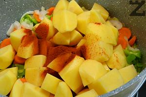 Добавят се картофите и поръсват с червен пипер. Налива се 1.5 л. гореща вода и посолява.