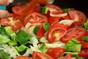 Нарязваме доматите на филийки или полумесеци. Слагаме ги при останалите зеленчуци. Поръсваме с червен пипер, посоляваме, добавяме 2 щипки захар.