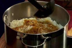 """Поръсваме отново с """"Чар масала"""" и заливаме със соса от свареното телешкото месо. Най-отгоре изсипваме задушените моркови, стафиди и бадеми. С върха на нож правим няколко дупки в ястието, за да може да излиза парата нагоре."""