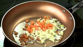 В тиган се загрява олио и за минута се запържват зеленчуците. Нарязват се на ситно чесън и целина и добавят в тигана. Посоляват се.
