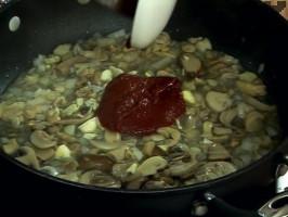 След като течността се редуцира, прибавяме наситнения чесън и доматеното пюре.
