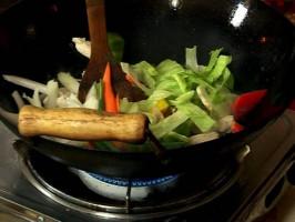 В уок се загрява олио и се пържи за 4-5 минути пилешкото филе. Добавя се счукания чесън, черен пипер, захар, сол и чубрица.Слагат се зеленчуците и се пържат за 2-3 минути.