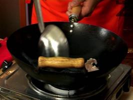 В уок се смесва масло, олио и синапено олио, загряват се и се запържва за 3 минути пилешкото месо нарязано на дребно.